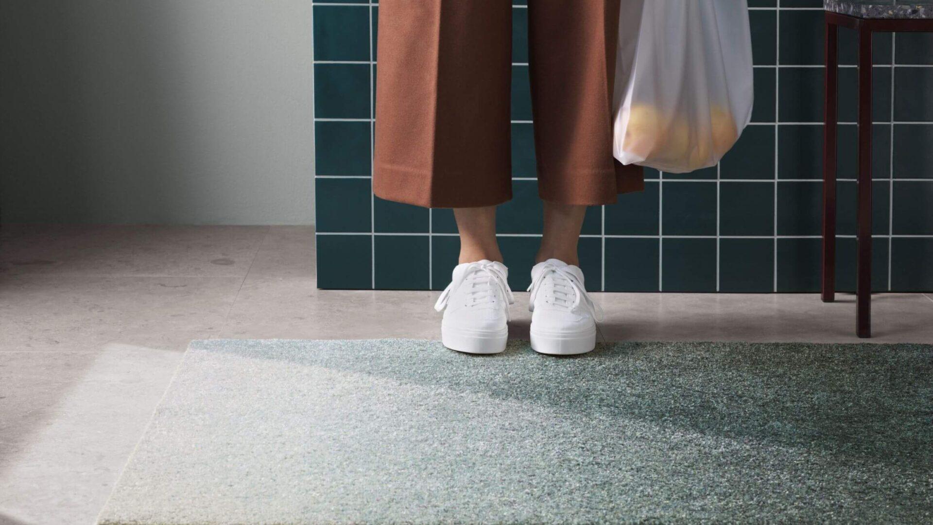 Matte og person med oransje bukser, hvite sko